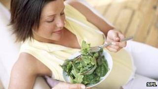 Pregnant woman eating salad