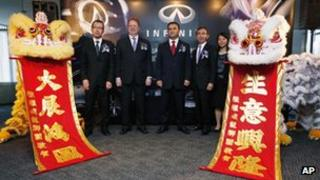 Carlos Ghosn, centre, poses with other Nissan executives during the opening ceremony for the new headquarters of its upscale Infiniti brand
