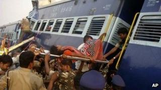 Rescuers evacuate an injured woman from the site of a train accident at a station near Penukonda, Andhra Pradesh
