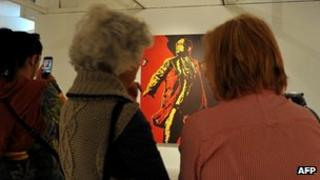 """Women look at the painting """"The Spear"""" by Brett Murray at the Goodman Gallery in Johannesburg on May 18, 2012"""