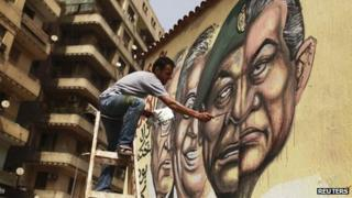 An artist paints the faces of Amr Moussa and Ahmed Shafiq and a combination of the faces of former president Hosni Mubarak and Field Marshal Mohamed Hussein Tantawi in Cairo May 22, 2012