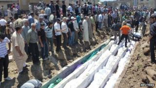 People gather for a mass funeral of those killed in Friday's attacks in Houla