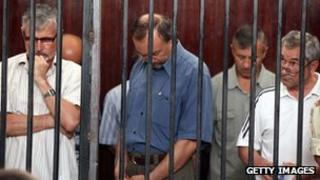 Some of the 24 men found guilty of being mercenaries are seen standing behind bars during their trial in Tripoli