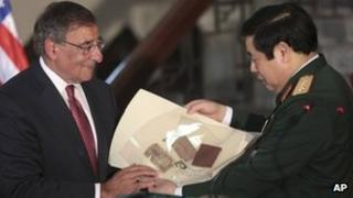 US Secretary of Defence Leon Panetta (L) hands his Vietnamese counterpart artefacts from the war