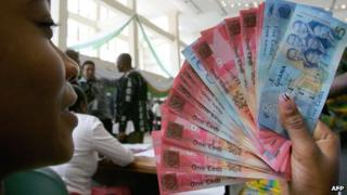 A woman with cedi notes