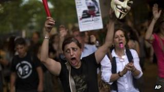Demonstrators shout slogans against the government during a protest in front a Bankia bank branch in Barcelona, Spain, Saturday June 2, 2012