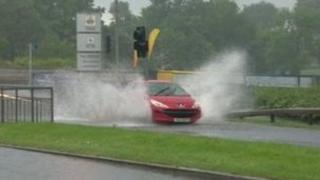Car driving through flooded road in Lisburn