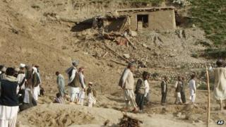 Afghans stand at the site after an earthquake hit Baghlan province, north of Kabul, Afghanistan, Monday, June 11, 2012