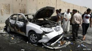 People inspect a car used in a bomb attack in Baghdad (16 June 2012)