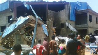 Bystanders look at the Sharon Church after it was struck by a suicide bomber's attack in Kaduna on 17 June 2012.