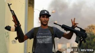 A rebel makes the victory sign in August 24 2011