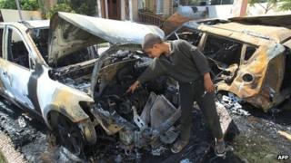 A Palestinian youth look at destroyed vehicles outside a home following an Israeli air strike on Gaza City on 20 June 2012