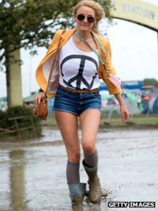 A festival goer braves the mud on day at The Isle of Wight Festival at Seaclose Park