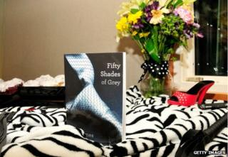 Fifty Shades of Grey by EL James, with high heel and whip on zebra skin rug