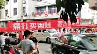 "The banner reads ""beat the traitors, drive them from the town"""