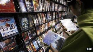 A customer looks at pirated film DVDs at a shop in Beijing (file photo)