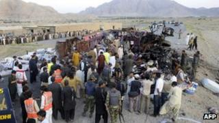 Pakistani security officials examine the wreckage of a destroyed bus after a bomb explosion on the outskirts of Quetta on June 28, 2012.