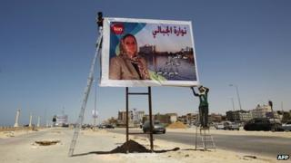 A worker installs a freshly printed election campaign poster of Nawara al-Jabali, a candidate for the upcoming General National Congress election in the eastern city of Benghazi on July 3, 2012.