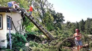 People clear fallen trees from their house in Grand Rapids, Minnesota 3 July 2012