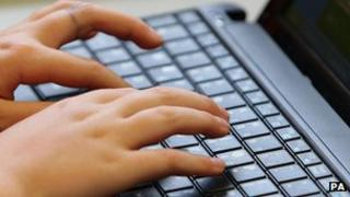 A person uses a laptop keyboard