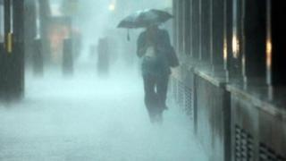 Woman walks with umbrella in heavy rain