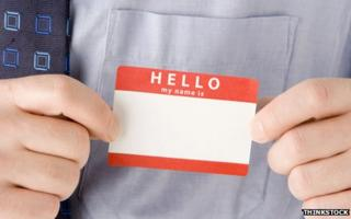 """Man putting on """"Hello - my name is"""" sticker"""