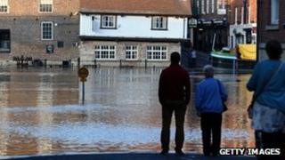 People watching rising water of River Ouse in York