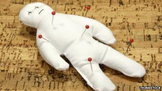Voodoo doll with pins on a corkboard