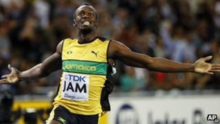 Usain Bolt sprinting in a yellow vest. His arms are stretched out to his sides in celebration.