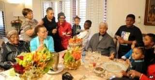 Former South African President Nelson Mandela celebrates his 94th birthday with his wife Graca Machel, second from left front, and other family members at his home in Qunu, South Africa, on Wednesday