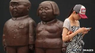 A Chinese woman uses a mobile in front of two statues in Beijing