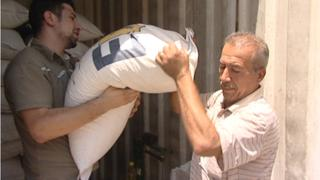 Construction worker Daoud carrying a bag of rice
