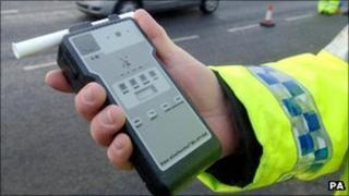 A police officer holds a breath test kit