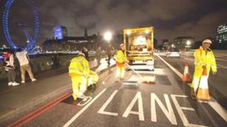 Workers painting and covering signs on Westminster Bridge in central London