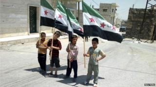 Four children holding up Syria flags