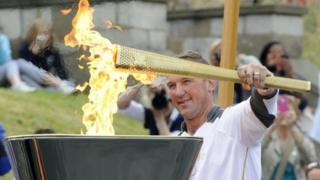 Four-time Olympic gold medallist Matthew Pinsent with the Olympic flame