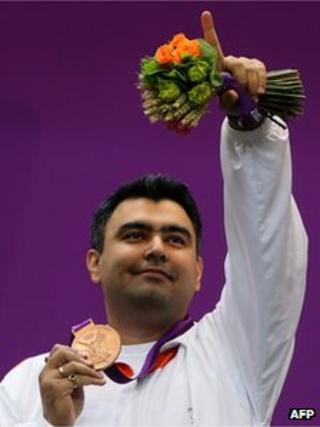 "Indian Gagan Narang celebrates at the podium after winning the bronze medal in the men""s 10m air rifle final during the London 2012 Olympic Games at the Royal Artillery Barracks in London on July 30, 2012."