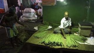 A vendor selling vegetables waits for customers at a vegetable wholesale market in the southern Indian city of Chennai July 16, 2012.