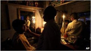 A man has a haircut by candle light in Calcutta, India (31 July 2012)