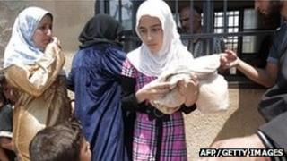 A Syrian girl carries a bag of bread (31 Jul)