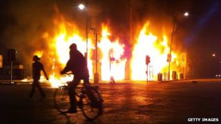 A Carpetright store burns on Tottenham High Road, in London, after being set on fire by rioters on 6 August 2011