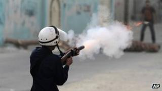 Bahrain policeman fires a tear-gas canister at a protester in Diraz (21 June 2012)