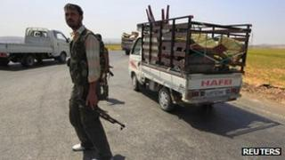 Fleeing civilians drive past a checkpoint manned by Members of Free Syrian Army on a road between Aleppo and Turkey 1 August 2012