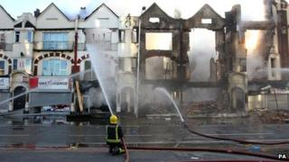 A Firefighter sprays water at some burnt houses