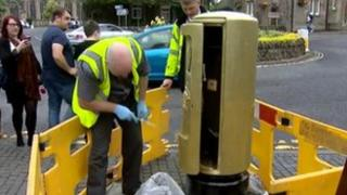 Crowd watches as a man paints a Royal Mail post box gold