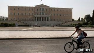 A cyclist passes the Greek parliament in Athens, 6 August