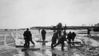 German workers clear snow throughout the night at an airfield, as the Berlin Airlift is temporarily delayed by the weather.