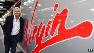 Sir Richard Branson next to a Virgin Pendolino train