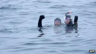 French amputee swimmer Philippe Croizon (R), and his friend swimmer Arnaud Chassery, celebrate after swimming between islands in the icy Bering Strait on 18 August 2012