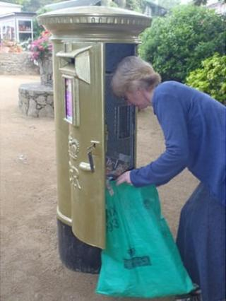 Sark gold postbox being emptied